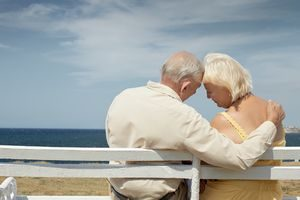 senior caucasian couple sitting on bench near the sea and hugging. Horizontal shape, rear view, copy space